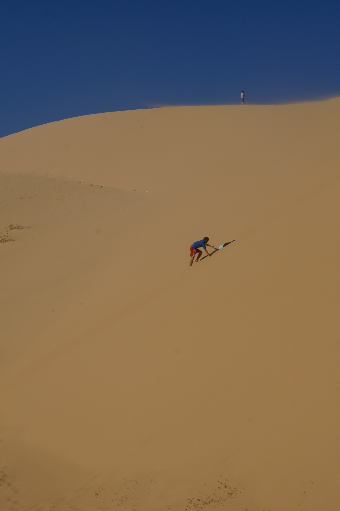 Brian attempting to sand board down the dunes!