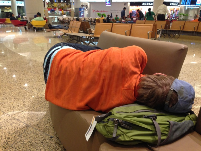 "Brian sleeping on a hard ""couch"" at 3 AM in Mumbai's airport during a layover."