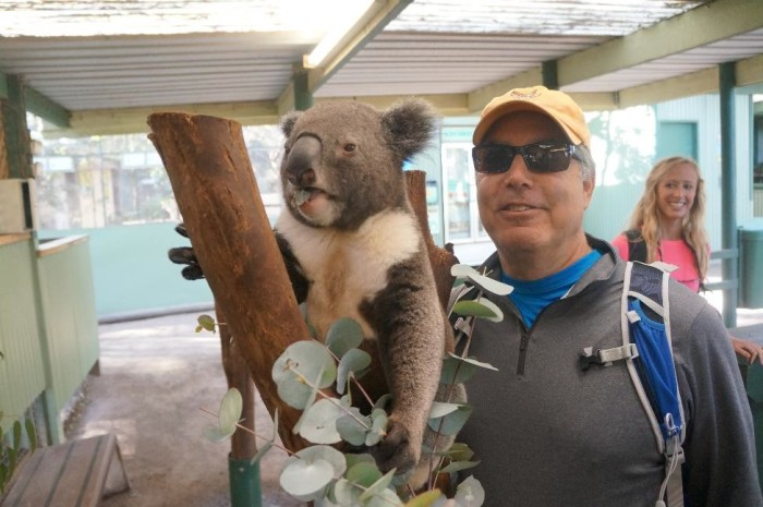 Larry posing with a rambunctious little koala.